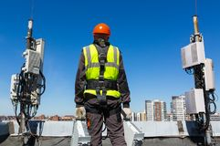 Professional industrial climber in helmet and uniform holds telecomunication equipment in his hand and antennas of GSM. Telecommunication engineer  in helmet and royalty free stock photo