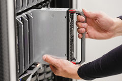 IT professional installs server cluster in large datacenter Stock Image