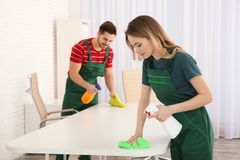 Professional janitors cleaning table in office. Hired help royalty free stock image