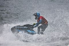 Professional jet ski riders compete at the IFWA World Tour. Jet Ski Championship. Contestants perform tricks for judges in the waves. Freeride World Stock Photography