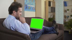Professional journalist typing article on laptop with green screen, freelance. Stock footage stock footage