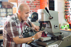 Professional key cutter making door keys copies. In locksmith stock image
