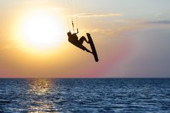 Professional kiter doing a complicated trick on a beautiful sunset background stock photography