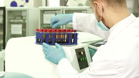 A professional lab technician checks each of the tubes before loading them into a laboratory centfruge. The lab assistant put the stand with test tubes on the stock footage