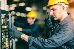 Free Professional Labor Worker Engineer Monitor At Machine Control Panel And Radio Talking Communication With Coworker During Press The Royalty Free Stock Image - 174032186