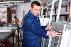 Professional labour with finished PVC profiles and windows at fa. Smiling professional labour with finished PVC profiles and windows at factory stock images