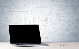Laptop on desk with business charts on wall Royalty Free Stock Image