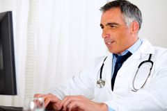 Professional latin doctor using a computer Stock Photos