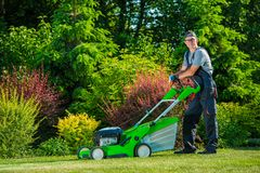 Professional Lawn Mowing. Smiling Professional Gardener with His Gasoline Lawn Mower. Professional Summer Landscaping Works royalty free stock photos