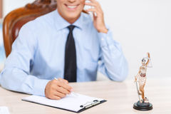 Professional lawyer sitting at the table. Busy lawyer. Close up of  professional smiling delighted lawyer writing and talking on mobile phone while having Royalty Free Stock Photos