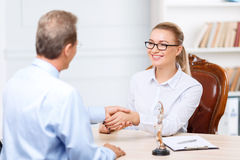 Professional lawyers having conversation. Great deal. Pleasant upbeat professional lawyer sitting at the table and shaking hands while having conversation Royalty Free Stock Images
