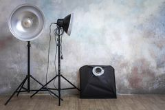 Professional lighting equipment in the photo studio on the original gray background. Minimalist interior and lighting equipment royalty free stock photos