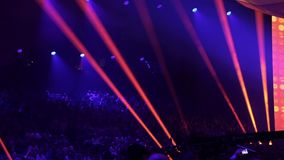 Concert hall with spectators. Professional lighting equipment on stage during a performance of popular artist. Hall with laser and light rays emanating from stock video footage