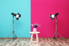 Professional lighting equipment and vase with flowers on table near wall in photo studio stock image