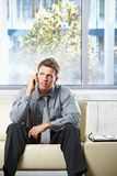 Professional listening to phonecall on sofa. Elegant professional listening to call on cell phone sitting on beige leather sofa in sunlit room Royalty Free Stock Photography