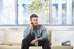 Professional listening to phonecall on sofa. Elegant professional listening to call on cell phone sitting on beige leather sofa in sunlit room Stock Photos