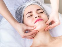 Professional lymphodrainage facial massage The cosmetologist is touching the client`s chin Royalty Free Stock Photos