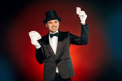 Professional Occupation. Magician in suit gloves and hat standing isolated on wall making tricks with cards show smiling royalty free stock photo