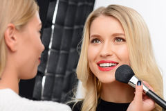 Professional make up applying procedure. Skin smoothing. Smiling young model in the process of face powder applying royalty free stock image