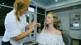 Professional make-up artist applying cream base to blond long curl hair and blue eyes model skin. stock video