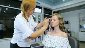 Professional make-up artist applying cream base to blond long curl hair and blue eyes model skin. stock footage