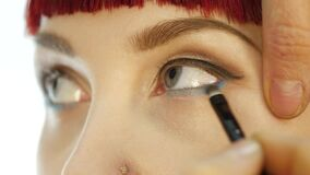 Professional make-up artist applying eyeliner on eye. makeup and fashion concept stock footage