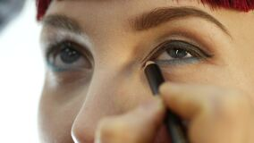 Professional make-up artist applying eyeliner on eye. makeup and fashion concept stock video