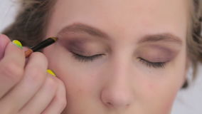 Professional make-up artist applying eyeshadow stock video footage