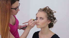 Professional make-up artist applying eyeshadow. Professional make-up artist applies eye shadow to eyelid of model in white room. Beauty, makeup and fashion stock video