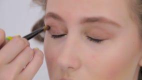 Professional make-up artist applying eyeshadow stock footage