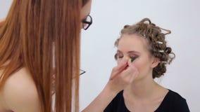 Professional make-up artist applying eyeshadow stock video footage