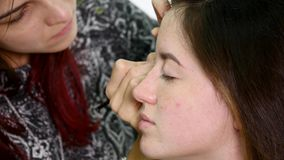 Professional make-up artist applying eyeshadow to model eye using special brush. Natural makeup in salon. Beauty, makeup. And fashion concept stock video