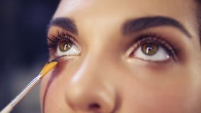 Professional make-up artist applying eyeshadow to model eye using special brush. Natural makeup in salon. Beauty, makeup. And fashion concept. Slowmotion shot stock footage