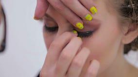Professional make-up artist applying false eyelashes on model`s eyes stock footage