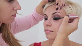 Professional make-up artist applying mascara on eyelashes of model stock video footage