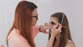 Professional make-up artist combing eyelashes of model stock video footage
