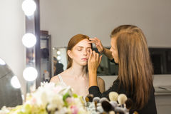 Professional Make-up artist doing glamour model makeup at work Royalty Free Stock Images