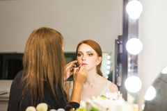 Professional Make-up artist doing glamour model makeup at work Stock Photo