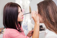 Professional Make-up artist doing glamour model makeup at work. Professional makeup artist working with beautiful young woman Stock Photos