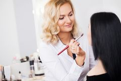 Professional Make-up artist doing glamour model makeup at work. Professional makeup artist working with beautiful young woman Royalty Free Stock Image