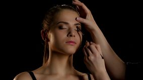 Professional make-up artist feathering light eyeshadow on the eyelid. Close-up stock footage