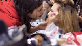 Professional make-up artist and hairdresser prepares woman to the performance. Makeup artist draws woman`s eyes with pencil. Hairdresser makes the hairstyle for stock video