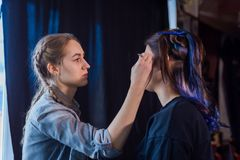 Make-up artist and hairdresser working with woman client stock photos