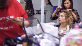 Two professional stylists makes scenic character for young woman in theatre. Professional make-up artist makes a beautiful greasepaint to the actress in theatre stock video