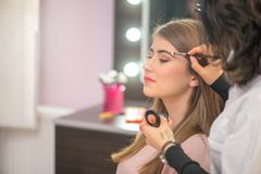 Professional make-up artist preparing model for studio shot. Make up royalty free stock images