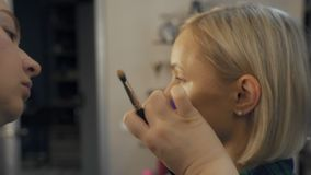 Professional make-up artist at work brush hand closeup - beauty fashion industry cosmetics backstage professional makeup. Side view macro beautiful natural stock video footage