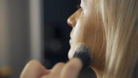 Professional make-up artist at work brush hand closeup - beauty fashion industry cosmetics backstage professional makeup. Side view macro beautiful natural stock footage