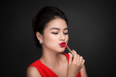 Free Professional Make-up. Attractive Asian Model Applying Red Lipstick. Royalty Free Stock Photography - 90933107