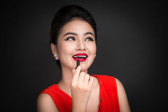 Free Professional Make-up. Attractive Asian Model Applying Red Lipstick. Stock Images - 91496374