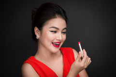 Free Professional Make-up. Attractive Asian Model Applying Red Lipstick. Stock Photo - 92637000